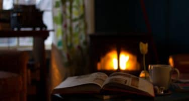 reading a book by a fireplace
