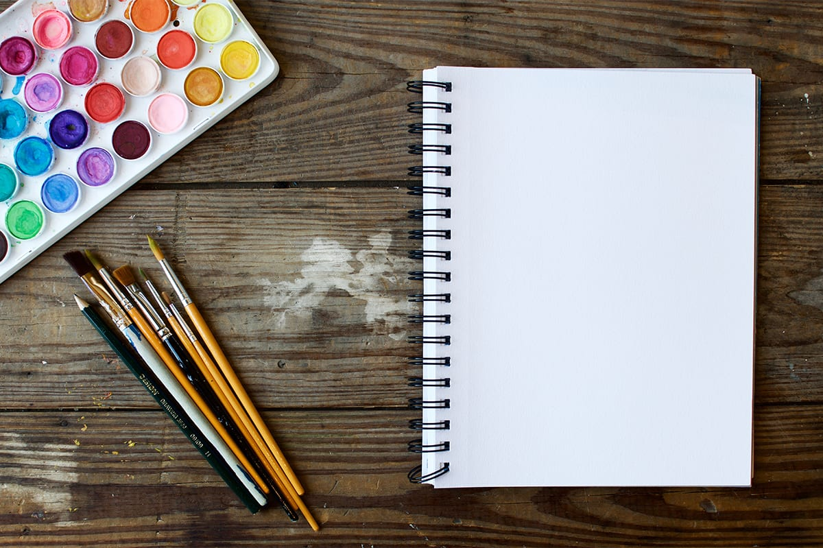 blank sketch book with paints and brushes nearby