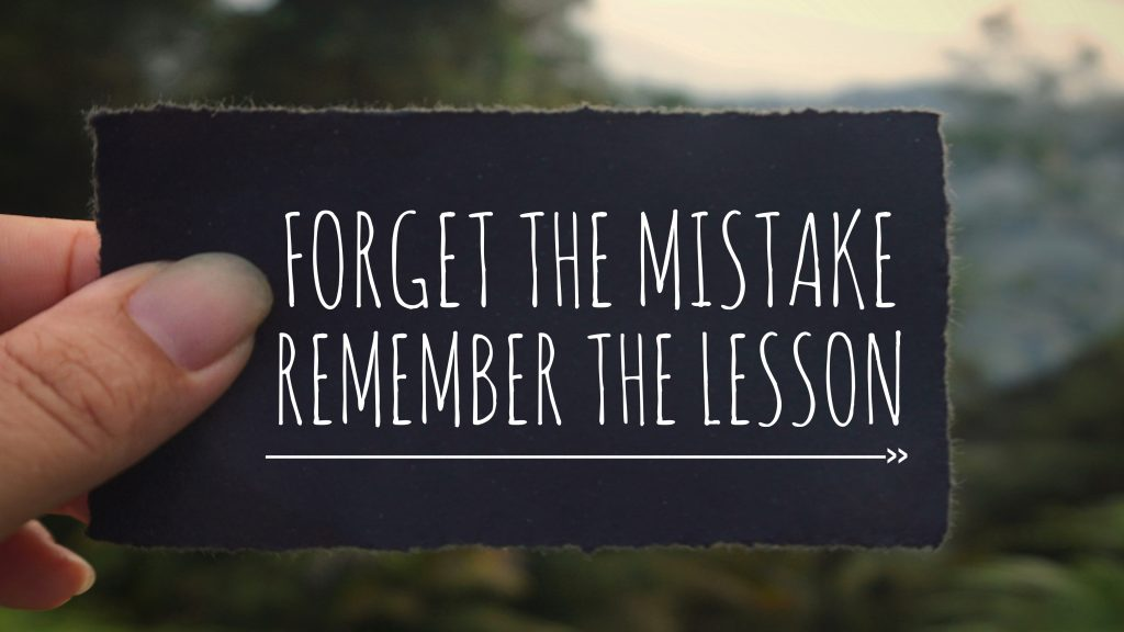 'Forget the mistake, remember the lesson' written on a black paper.