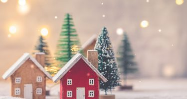 Miniature wooden houses over blurred Christmas decoration background
